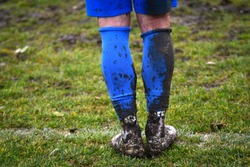 Muddy football - soccer player standing on the line / Muddy boots