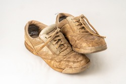 Muddy gardening shoes on a white background