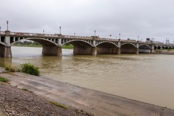 Muddy river water flowing under the bridge