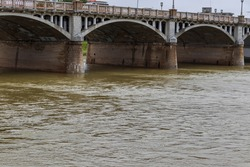 Muddy river water flowing under the concrete bridge