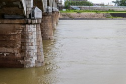 Muddy water flowing under a concrete bridge