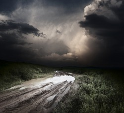 Muddy wet countryside road and dark storm clouds