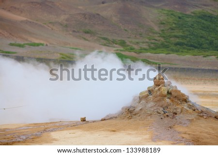 Mudpot in the geothermal area Hverir, Iceland. The area around the boiling mud is multicolored and cracked. Vertical view