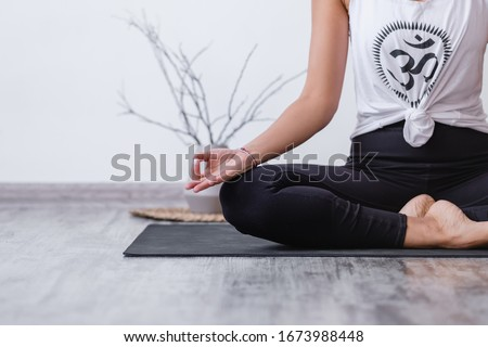 Mudra gesture. Relaxed harmonious beautiful brunette woman yoga instructor doing lotus position. Yogi girl sitting on rug floor during workout. Copyspace. Cropp. Translate: Buddhism Symbol Сток-фото ©
