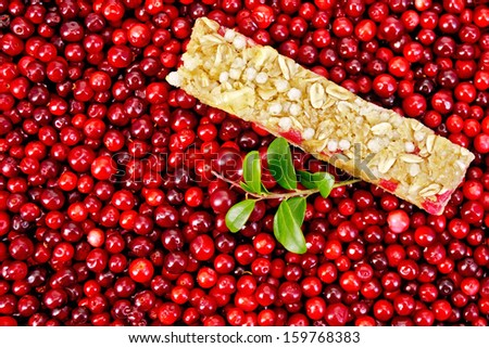 Muesli bar, twig with leaves and berries lingonberry background of lingonberry