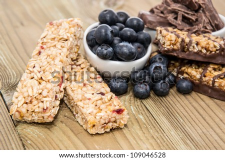 Muesli Bars with Blueberries and Chocolate on wooden background