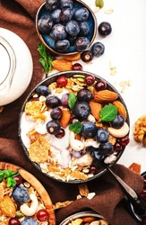 Muesli bowl and ingredients for healthy breakfast. Granola, nuts, blueberry, cranberry, oatmeal, greek yoghurt, whole grain flakes on white table