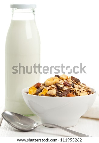 Muesli in bowl with bottle of milk in the background