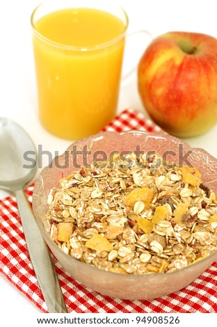 muesli of oats, glass of juice and apple isolated on white