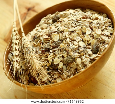 muesli of oats with raisin in wooden bowl