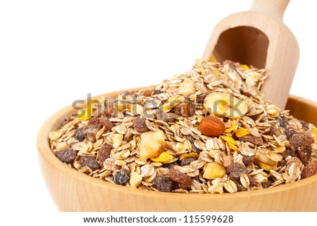 Muesli with dried fruits in wooden bowl isolated on white background
