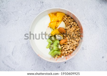 Muesli with fresh fruits and yogurt. Ingredients for cooking healthy breakfast. Flat lay, gray background. Foto stock ©