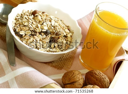 muesli with raisins in bowl, glass of orange juice - healthy breakfast