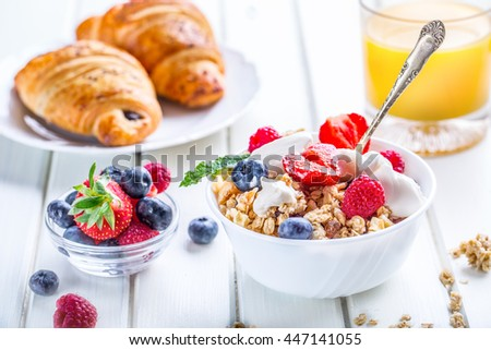 Muesli with yogurt and berries on a wooden table. Healthy fruit milk yogurt and cereal brakfast.