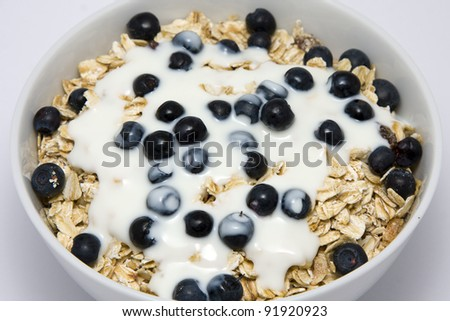 Muesli with yogurt and blueberries on a white plate