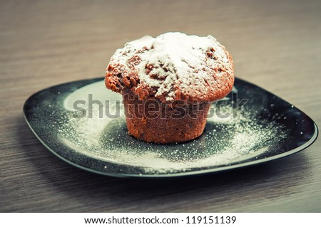 Muffin chocolate cake with white powdered sugar on a black plate