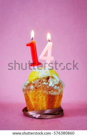 Muffin with burning birthday candles as number fourteen on pink background #576380860
