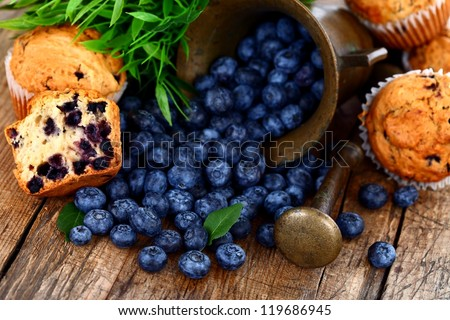 Muffins and blueberries on rustic wooden table