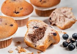 muffins wit blueberries and knive aside on a woodchopper