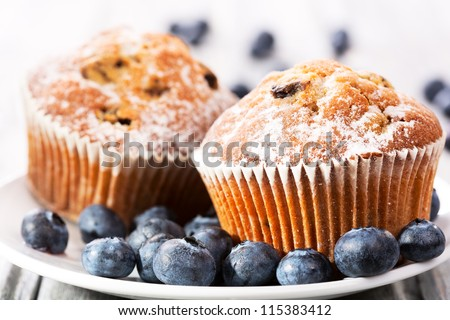 muffins with fresh blueberries on wooden table