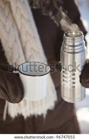 Mug and thermos of hot chocolate on a cold winter day