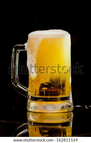 Mug fresh beer on a black background
