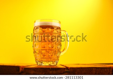 Mug full of light lager beer on a wooden table over a bright yellow background