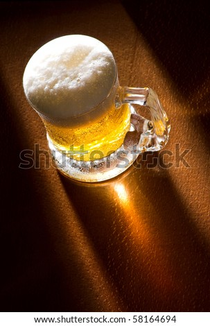 Mug of beer close up on wooden table, spot back-light,  selective focus