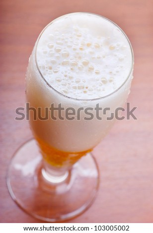 Mug of beer on a table. View from above