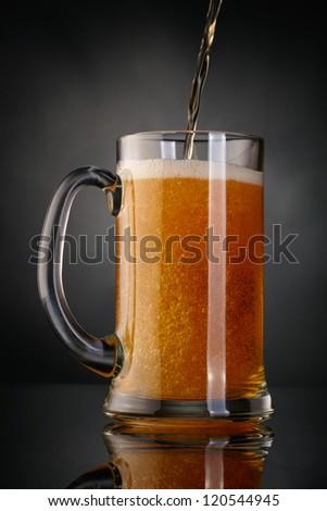 Mug of beer over dark background