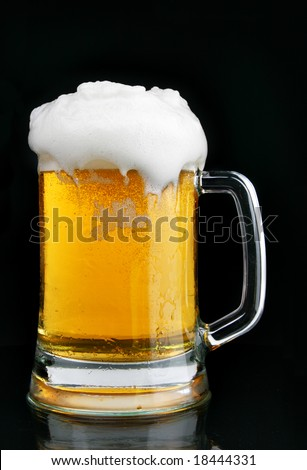 Mug of beer with froth over black background
