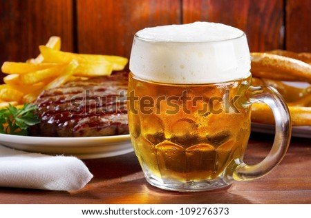 mug of beer with grilled meat - stock photo
