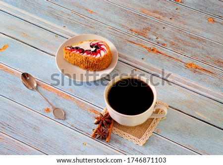 Mug of black coffee on a napkin with anise and a biscuit cake saucer. Close up shot.