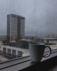 Mug of coffee or tea siting by the windown on a rainy day. The mood is calm and cold, european feeling.