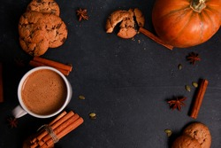 Mug of coffee with milk and foam, spices, orange pumpkins, seeds, cookies on black table. Autumn drink concept. Fall, spicy latte, home, pastry, thanksgiving, coffee shop menu, top view