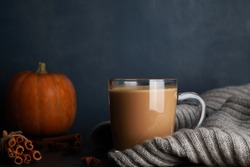 Mug of coffee with milk, blurred orange pumpkin, cinnamon and grey woolen scarf on black table against blue background. Autumn drink concept. Fall, spicy latte, thanksgiving, coffee shop menu, closeup