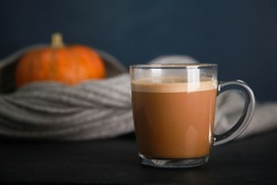 Mug of coffee with milk foam, blurred orange pumpkins and grey woolen scarf on black table against blue background. Autumn drink concept. Fall, spicy latte, thanksgiving, coffee shop menu, closeup
