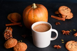 Mug of coffee with milk foam, spices, orange pumpkin, seeds, cookies on black table. Autumn drink concept. Fall, spicy latte, home, pastry, thanksgiving, coffee shop menu, closeup