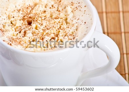 mug of coffee with whipped cream and cinnamon on bamboo mat
