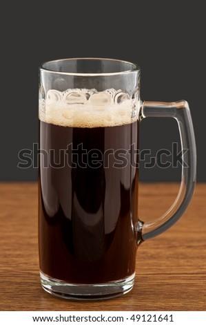 Mug of dark beer on wooden counter