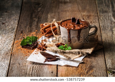 Mug of hot chocolate with cinnamon sticks over dark wooden background.