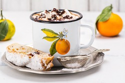 Mug of hot chocolate with small marshmallows in vintage mug with tangerin and christmas stollen over white background. Selective focus
