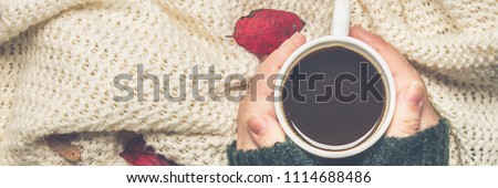 Mug of hot coffee in a woman's hand in a sweater in the autumn setting on a wooden table with a knitted scarf, sweater. Comfort, warmth, cozy.. Banner