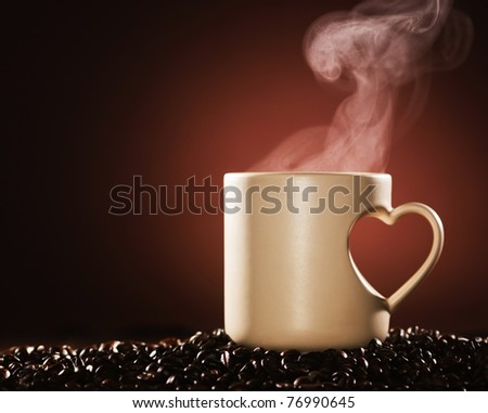Mug of hot coffee on coffee beans with rising steam