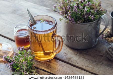 Mug of thyme healthy herbal tea, honey jar and rustic metal cup full of thymus serpyllum medicinal herbs. #1426488125