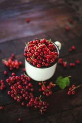 Mug overflowing with red berries on a wooden background. Berry scattered near a cup on a wooden table in the village. Flat lay