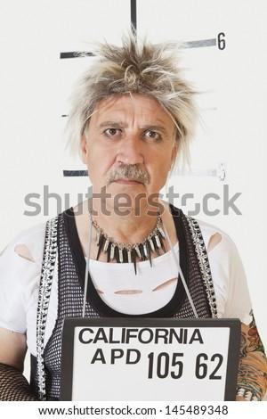 Mug shot of serious senior male punk