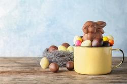 Mug with chocolate Easter bunny and candies on table