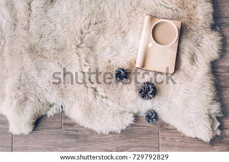 Mug with coffee and book on sheep skin rug. Winter weekend concept, top view