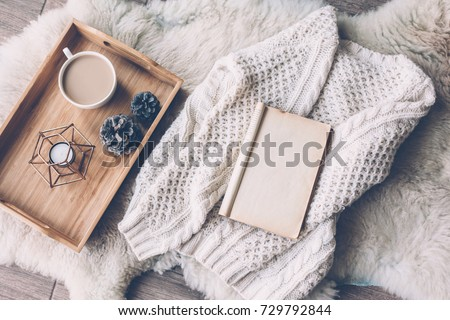 Mug with coffee and home decor on wooden serving tray on sheep skin rug. Warm sweater and open book, winter weekend concept, top view
